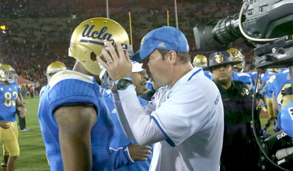 UCLA Coach Jim Mora embraces wide receiver Shaquelle Evans after the Bruins' 35-14 win over USC at the Coliseum on Nov. 30.