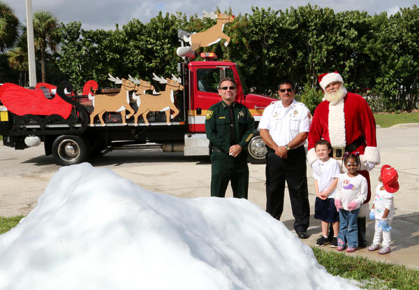 From left, Broward Sheriff Scott Israel, Broward Sheriff Fire Rescue Chief Tony Stravino and Santa Claus, aka Jerry Wilcox, are pictured in front of a mound of snow with three children at the Broward Sheriff Fire Rescue Deerfield Beach Fire Station #102 on Saturday.