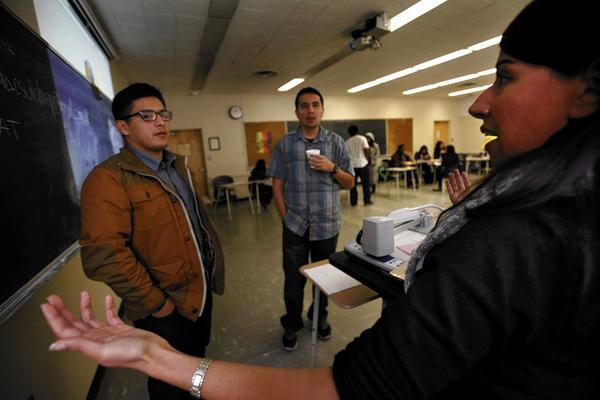 Carla Bracamonte, right, talks to students Gonzaga Mendez, 22, left, and Alex Moreno, 35, at Cal State L.A. about their options under Obamacare. Bracamonte is working for the California State University Health Insurance Education Project to explain the Affordable Care Act to students.