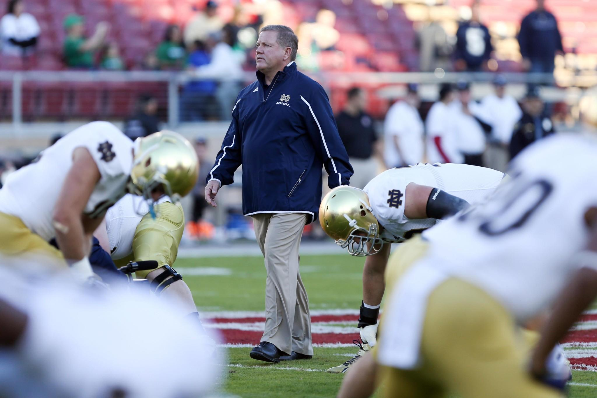 Notre Dame coach Brian Kelly walks amongst players before the game against Stanford.