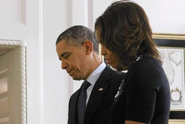 President Obama and First Lady Michelle Obama take a moment of silence for the 26 killed a year ago Saturday at Sandy Hook Elementary School. Gun safety legislation fell short in Congress after the massacre.