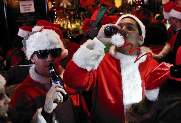 Revelers dressed as Santa Claus in New York City's East Village during the annual SantaCon bar crawl, which has some city residents concerned about public rowdiness.