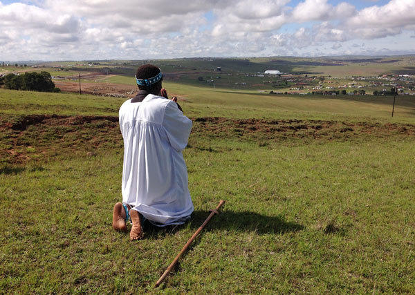 Shembe priest Michael Notychanga prays in the direction of the home of Nelson Mandela. In the distance is the dome where his funeral was held in Qunu, South Africa. , Sunday, Dec. 15, 2013. (t) ** Usable by LA and DC Only **