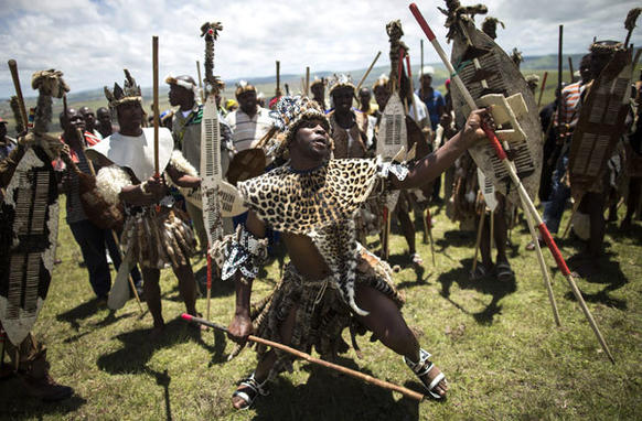 Men in Zulu warrior attire perform ritual dances at a public viewing area overlooking the burial ceremony for Nelson Mandela in his ancestral village of Qunu, South Africa.