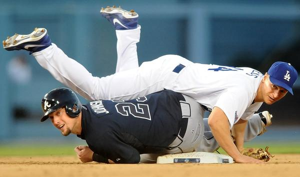 Los Angeles Dodgers second baseman Mark Ellis completes a double play as Atlanta Braves Elliot Johnson slides into second.