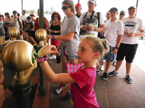 7-year-old Madison Laughman, with her mother (background) Nicole Laughman, holds up a wristband to check-in using the new MyMagic  turnstiles, at Main Street USA at the Magic Kingdom, Walt Disney, World, Thursday, August 15, 2013.