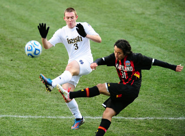 Maryland midfielder Tsubasa Endoh kicks the ball by Notre Dame's Connor Klekota during the first half of the NCAA Division I men's national soccer championship.