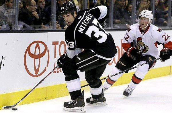 Kings defenseman Willie Mitchell controls the puck along the boards against Senators winger Erik Condra during a game earlier this season at Staples Center.