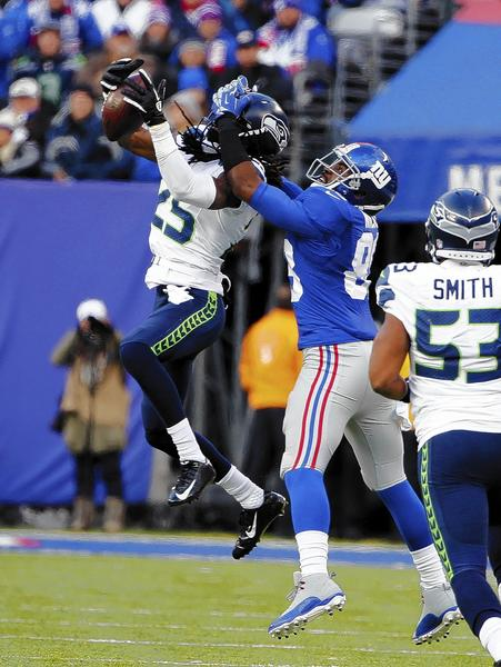 Seattle Seahawks cornerback Richard Sherman (25) intercepts a pass intended for New York Giants wide receiver Hakeem Nicks during the first half at MetLife Stadium.