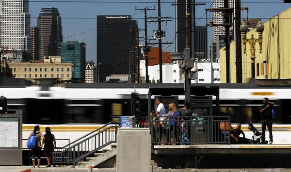 Metro Blue Line cars zip past a station near Washington Boulevard and Flower Street, where the Blue Line converges with the Expo Line. After the Expo Line opened, Angelenos who lived within a half-mile of a station tripled their rail ridership and reduced their daily driving by 40%, a USC study found.