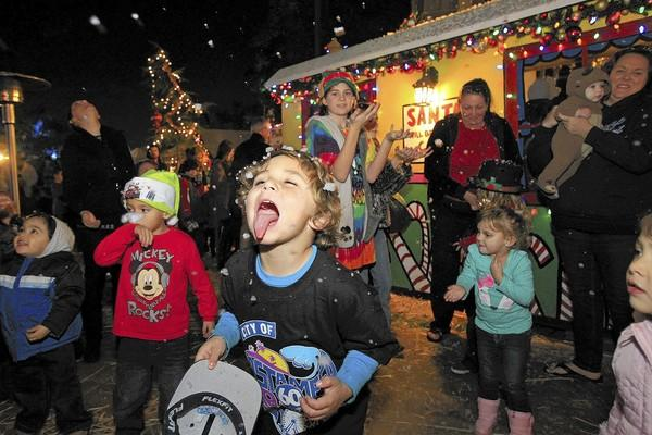 Nicky Johnson, 6, of Costa Mesa sticks his tongue out to catch snow during the opening for the Snoopy House at Costa Mesa City Hall on Friday.