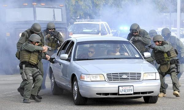Costa Mesa Police Department SWAT show their stuff as they surround a car and move in during a reenactment of a hostage situation during the 60th anniversary celebration of the CMPD on Sunday.