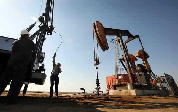 A wireline operator prepares a slick line at an oil pump jack site in the oil fields near Bakersfield.