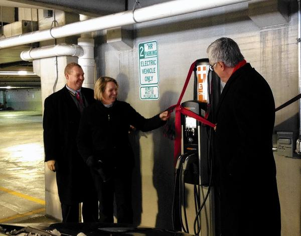 (From left to right) St. Charles Electric Services Manager Tom Bruhl, resident Julia Davies and Mayor Ray Rogina unveil the city's first electric vehicle charging station on Monday.