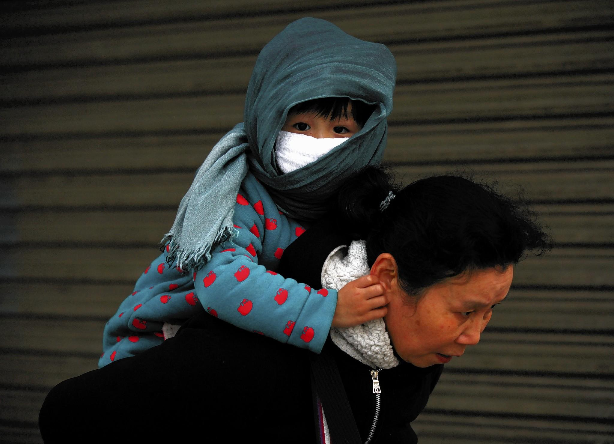 A grandmother carries a boy in smoggy Nanjing, China