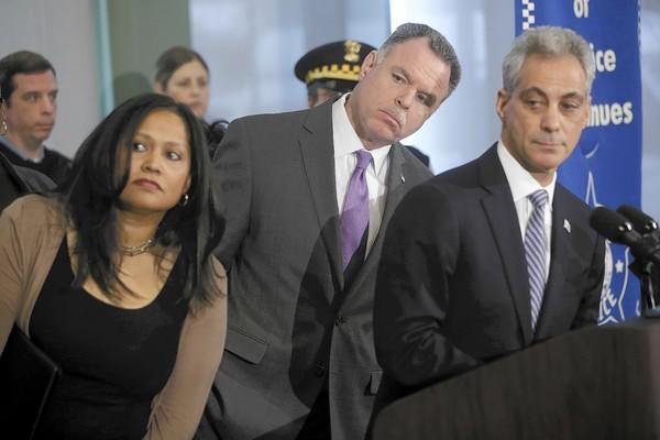 Family and Support Services Commissioner Evelyn Diaz, from left, Police Superintendent Garry McCarthy and Mayor Rahm Emanuel look at a map showing a citywide decrease in crime Monday at the Deering District police station.