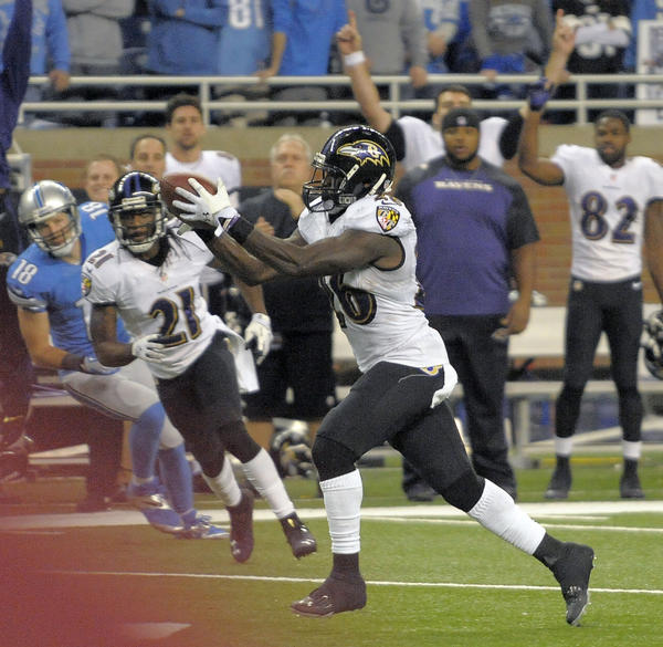 Raevns quarterback Matt Elam, right, intercepts a pass against the Detroit Lions in the fourth quarter, sealing the team's two-point victory.
