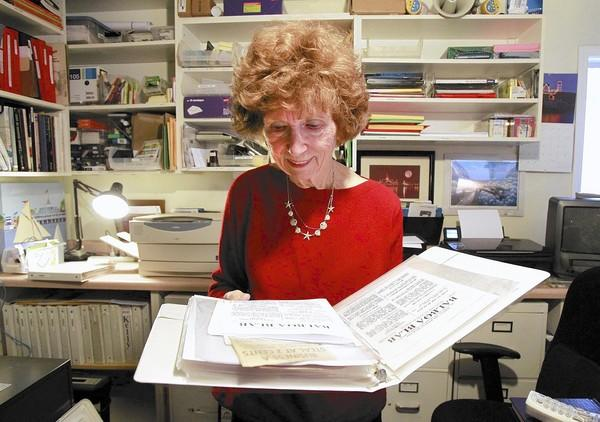 Gay Wassall-Kelly, longtime editor of the Balboa Beacon newsletter, looks at a binder of past editions of the newsletter in her home office surrounded by Balboa Island memorabilia.