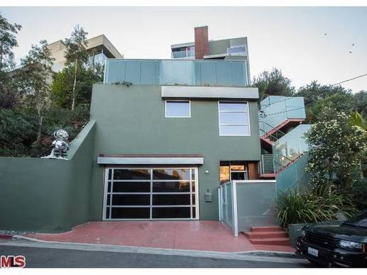 Green paint now covers the exterior of the home and the retaining wall, which owner Chris Brown had sprayed with graffiti.
