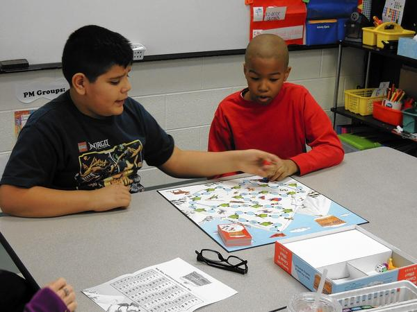 Field School 4th-grader Leo Gomez-Medina, left, plays a reading game with 5th grader Corey Lowery.