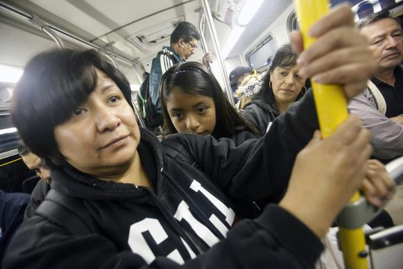 Carmen Mendoza and her daughter Nicole, 11, ride the 760 bus at the beginning of their 15-mile trek by MTA bus from their home in Bell Gardens to school and work in downtown L.A