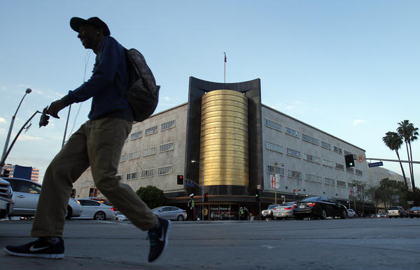 A pedestrian crosses the street near the May Co. building at the intersection of Wilshire Blvd. and Fairfax Ave. in Los Angeles.