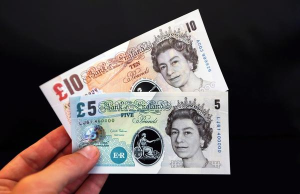 Samples of five- and 10-pound British polymer banknotes are displayed during a news conference at the Bank of England in London.