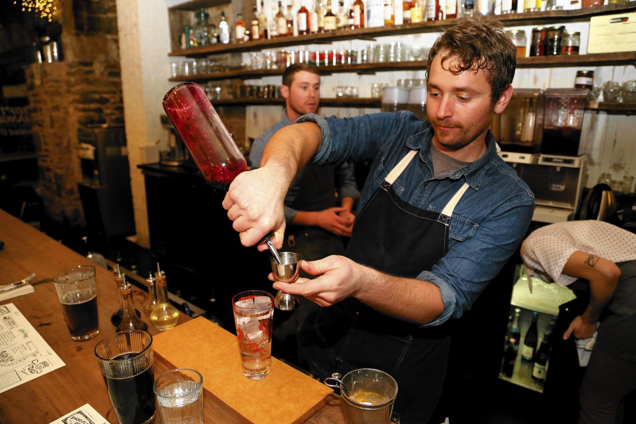 Bartender Patrick Gartnar makes a drink out of barrel-aged gin.
