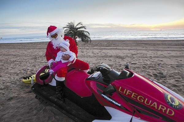 Melody Caldwell, 9 months old, poses for a picture with Santa Claus (Chris Egan) during the second annual Christmas on the Beach, hosted by the Huntington Beach State Lifeguards on Friday.
