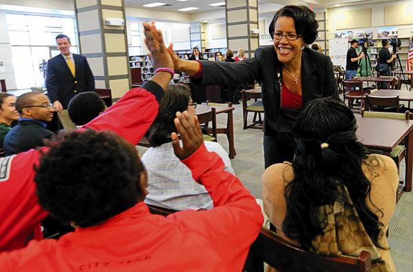 Superintendent Barbara Jenkins high-fives Oak Ridge High School faculty and staff members before a news conference to announce high school grades.