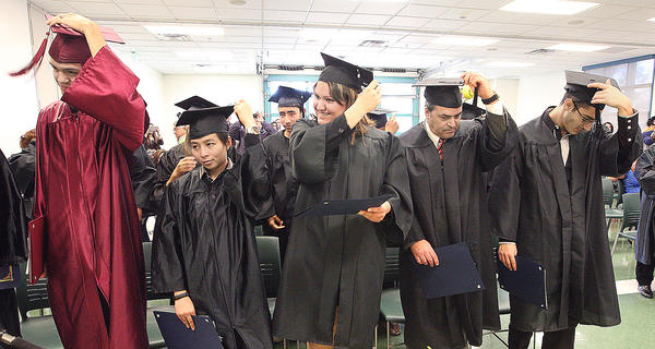 Graduates flip their tassels during the Glendale Community College GED program graduation ceremony on Tuesday, December 17, 2013.