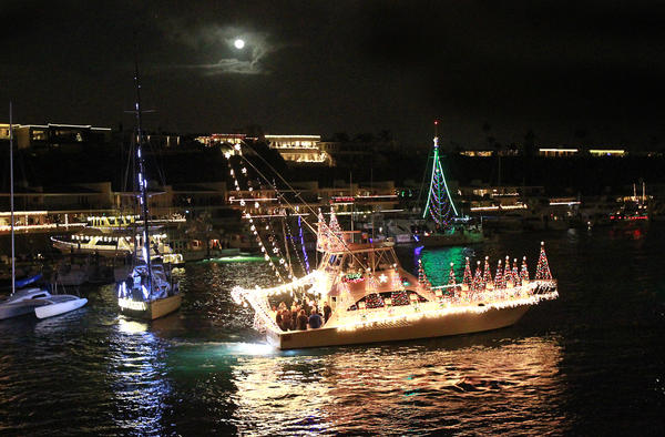 "The Quitena makes a turn near the Balboa Bridge under the full moon while participating in the ""Rockin Around the Christmas Tree"" 105th annual Newport Beach Christmas Boat Parade on Wednesday."