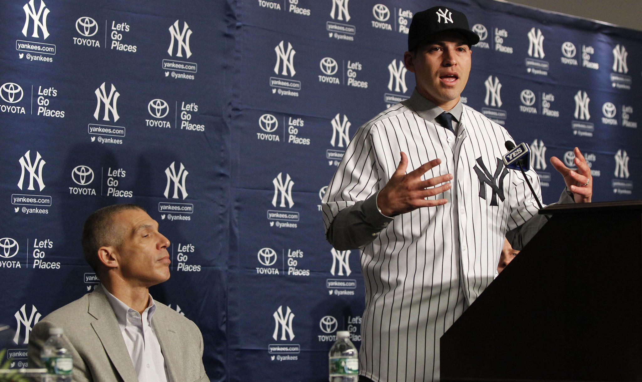 Dec 13, 2013; Bronx, NY, USA; New York Yankees new center fielder Jacoby Ellsbury talks during press conference as manager Joe Girardi watches at Yankees Stadium.
