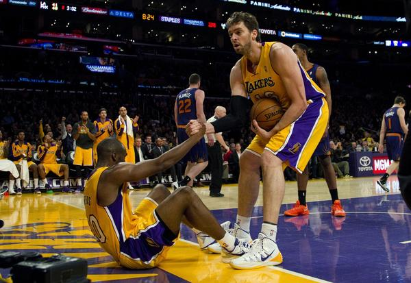 Lakers center Pau Gasol helps teammate Kobe Bryant to his feet after Meeks was fouled in Tuesday's game against the Phoenix Suns at Staples Center.