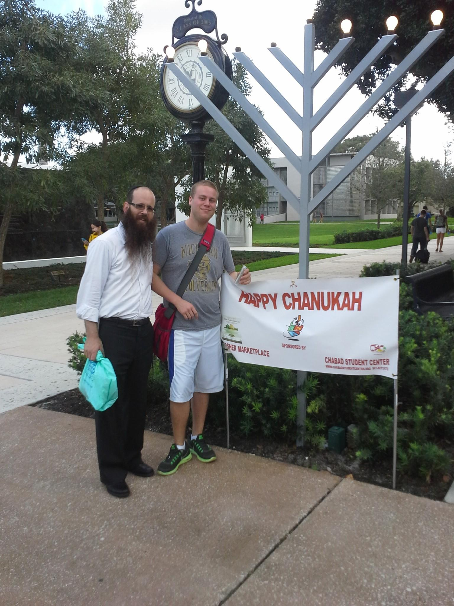 Rabbi Boruch Schmuel Liberow stands with Lynn University student Brett Ferber at the menorah when it was up at the campus earlier this month. The 9-foot menorah went missing this week from the rabbi's yard (courtesy photo).