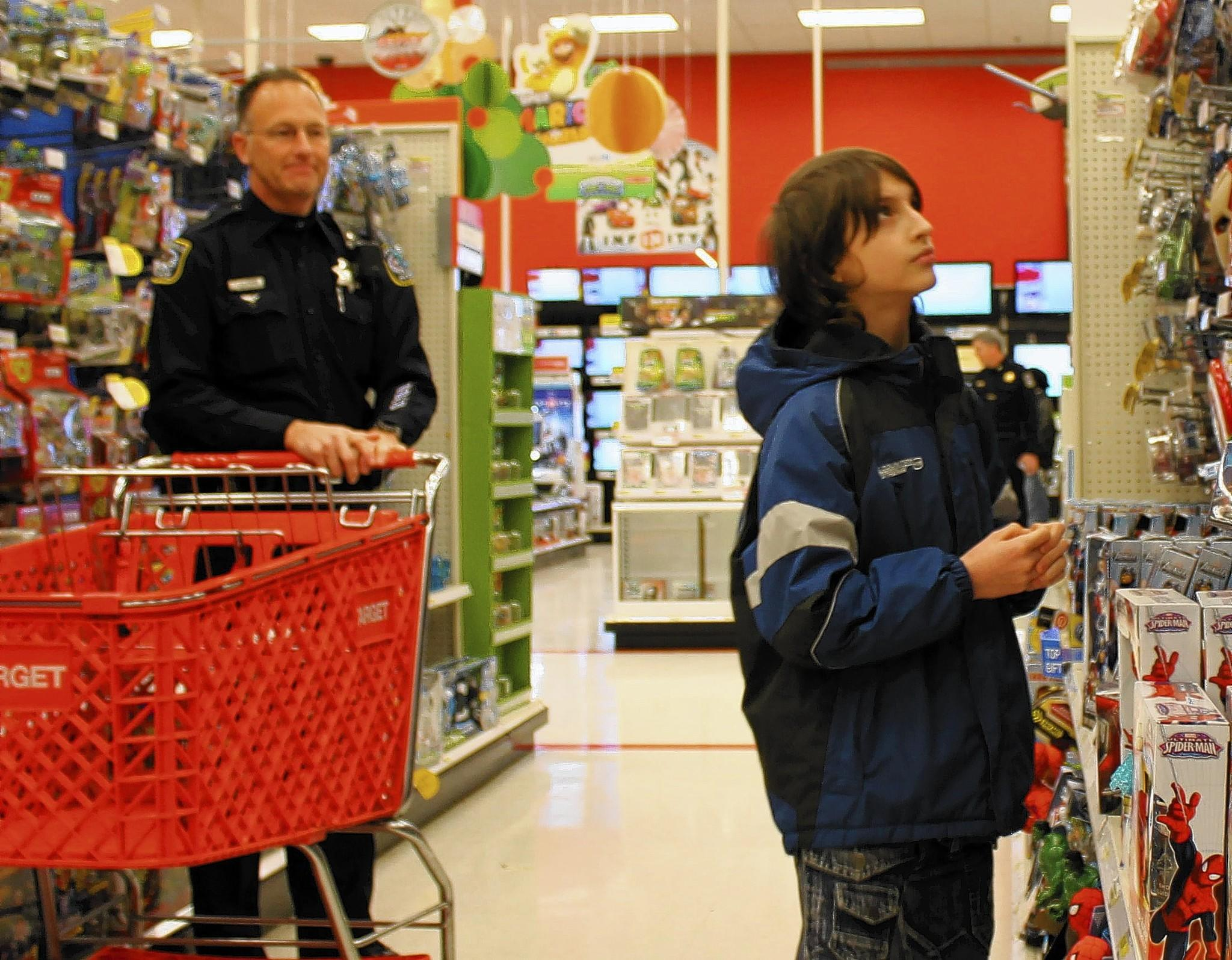 Kaon, 11, chooses a toy while Naperville police officer Dan Fisher waits with shopping cart.