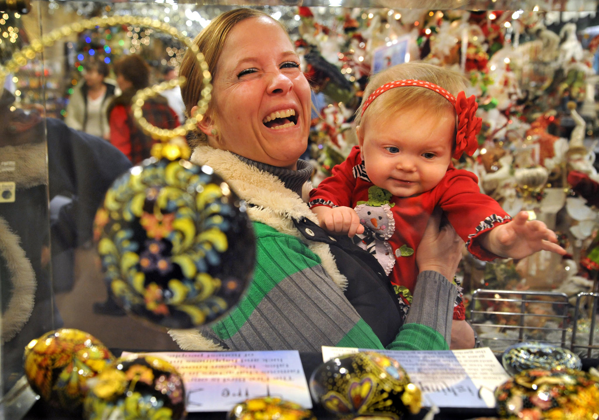 Stacey Huber of Jarretsville has to keep an eye on daughter Brynn Huber, who is interested in touching the delicate hand-painted ceramic ornaments from Uzbekistan, on display at Valley View Farms. Brynn will celebrate her first birthday next week. The large garden store emporium sells trees and every imaginable Christmas decoration and accessory from the second week in October through the holiday season.