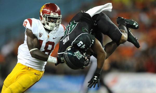 Hawaii's Donnie King Jr., right, is upended in front of USC safety Dion Bailey during the Trojans' season-opening win.