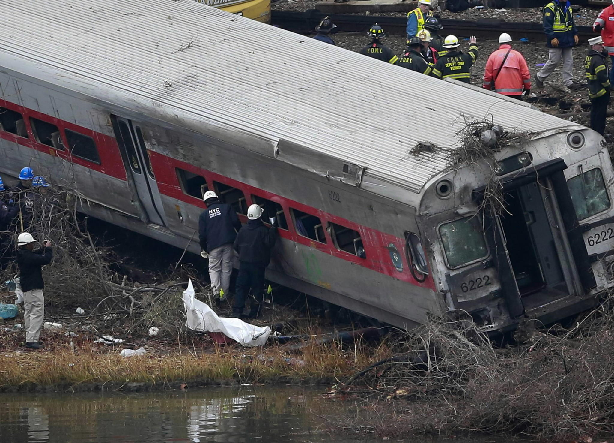 Emergency and track workers look at a derailed Metro-North train in the Bronx Dec. 2, the day after it crashed killing four people and injuring 11 critically. Inquiries have begun into the railroads operating procedures.