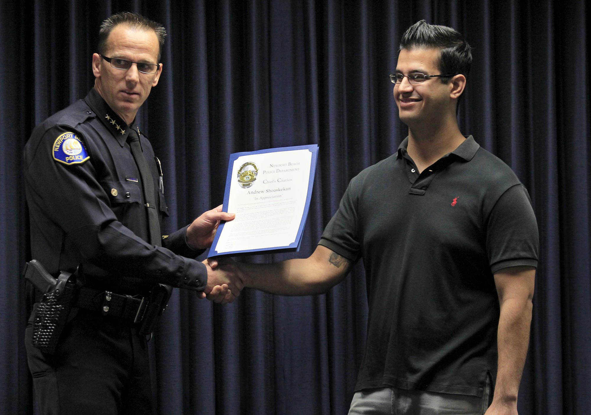 Newport Beach police chief Jay Johnson, left, hands Andrew Shoashekan a chief's citation during a ceremony at the Newport Beach Police Department on Thursday. Shoashekan was acknowledged for stopping a suicidal woman from jumping off an 18th floor balcony at Island Hotel in Newport Beach.