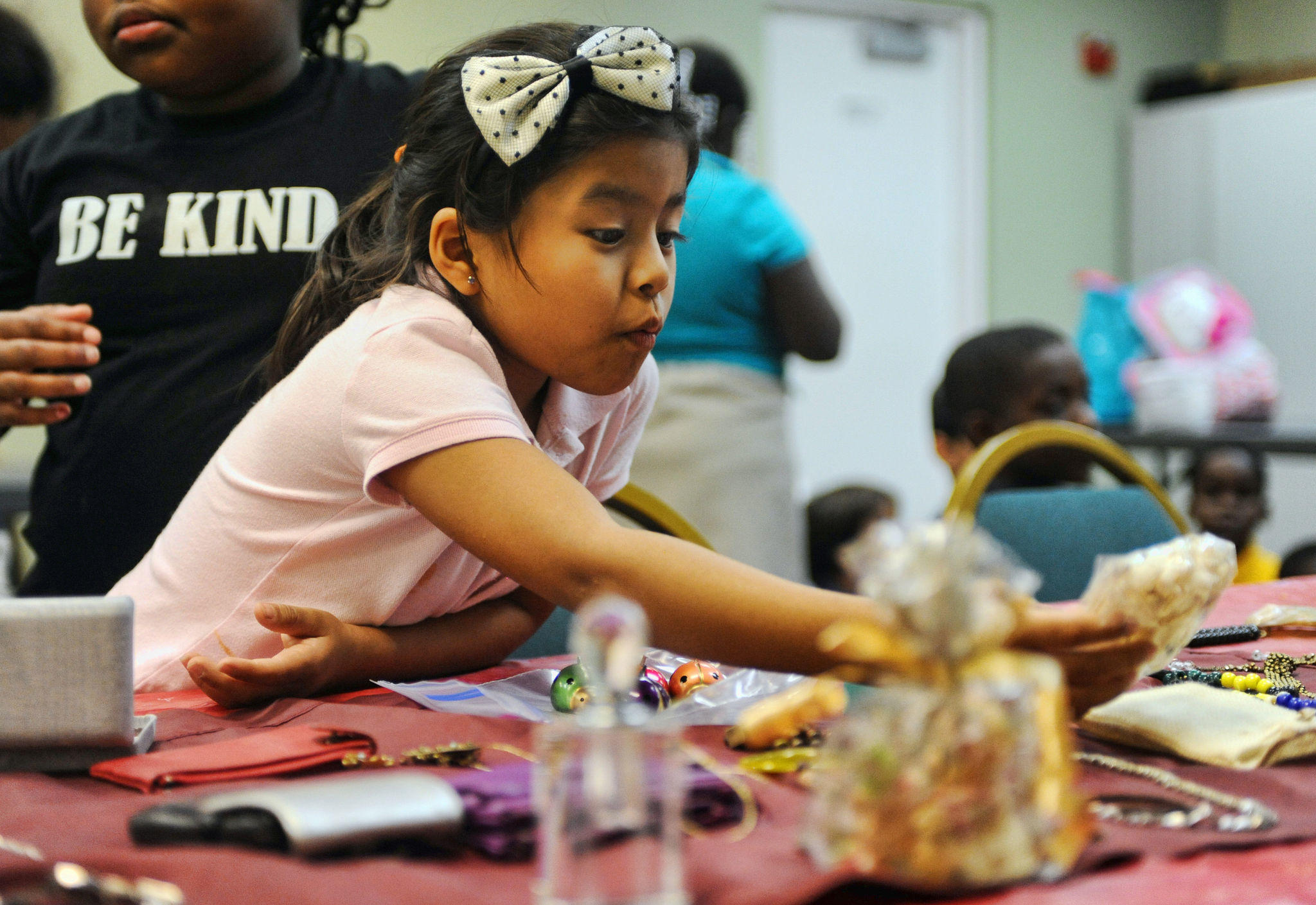 Alejandra Hernandez,7, takes part in a gift giving lesson at the Florence Fuller Development Center in Boca Raton. Students that participated were able to choose gift for their caretakers from a variety of donated jewelry and a variety accessories. The children then learned to wrap presents.12/19/12. Jim Rassol, Sun Sentinel.