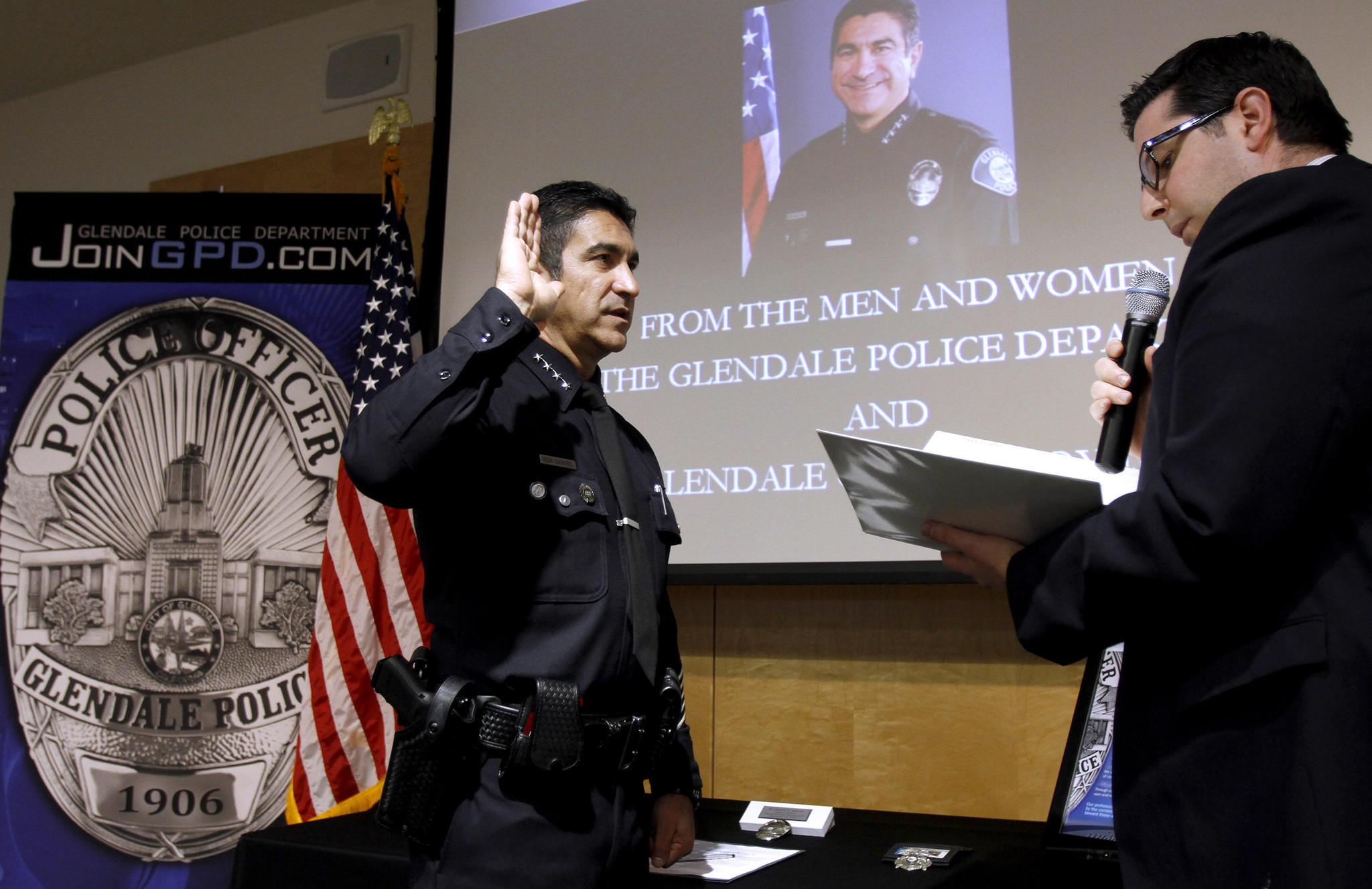 Glendale city clerk Ardashes Kassakhian, right, swears in the new Glendale Police chief Robert Castro, left, during a swearing in ceremony at the Glendale Police Dept. headquarters in Glendale on Thursday, Dec. 19, 2013.