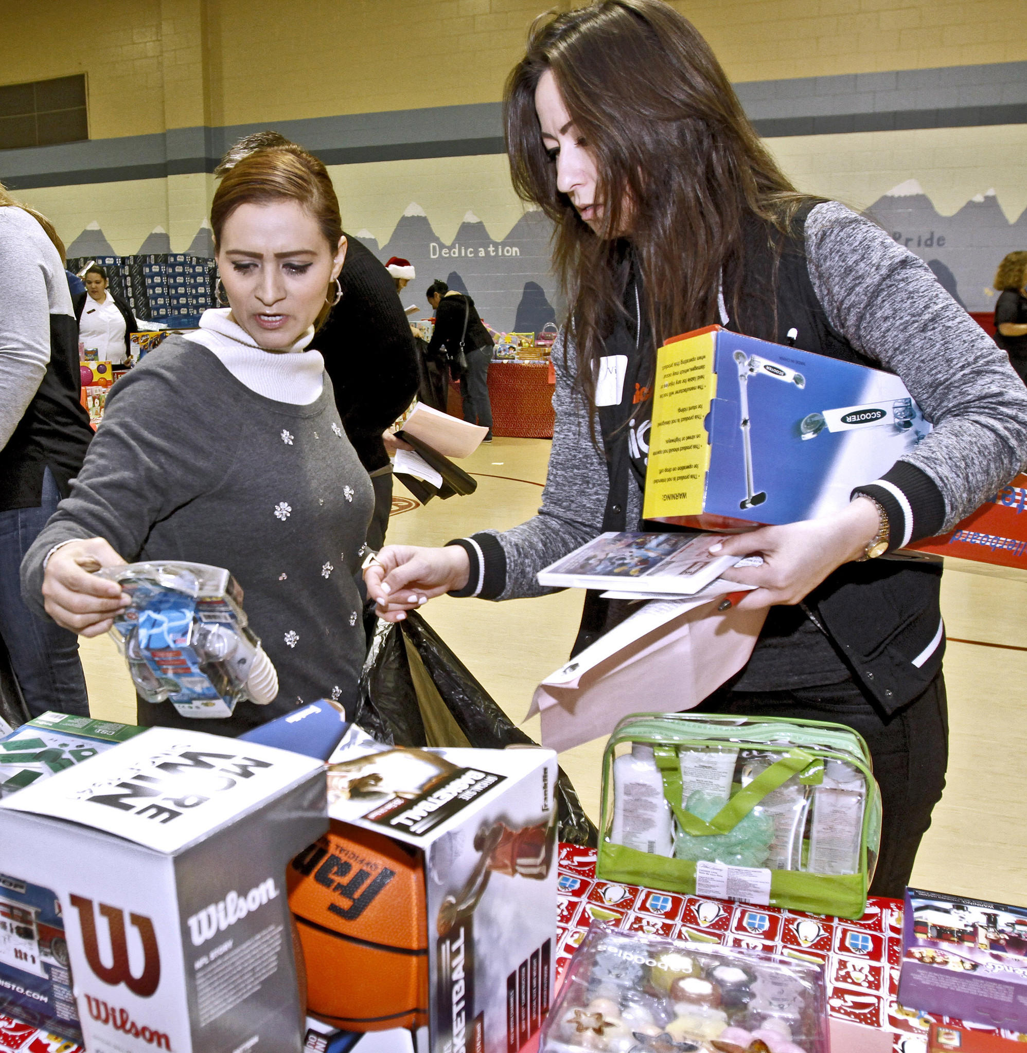 With the help of volunteer Victoria Wells, right, Rosario Ramirez, left, chooses games for her children during the Glendale Salvation Army toy distribution at the Corps gym in Glendale on Thursday, Dec. 19, 2013. About 500 local families were given toys for children up to 12 years old.