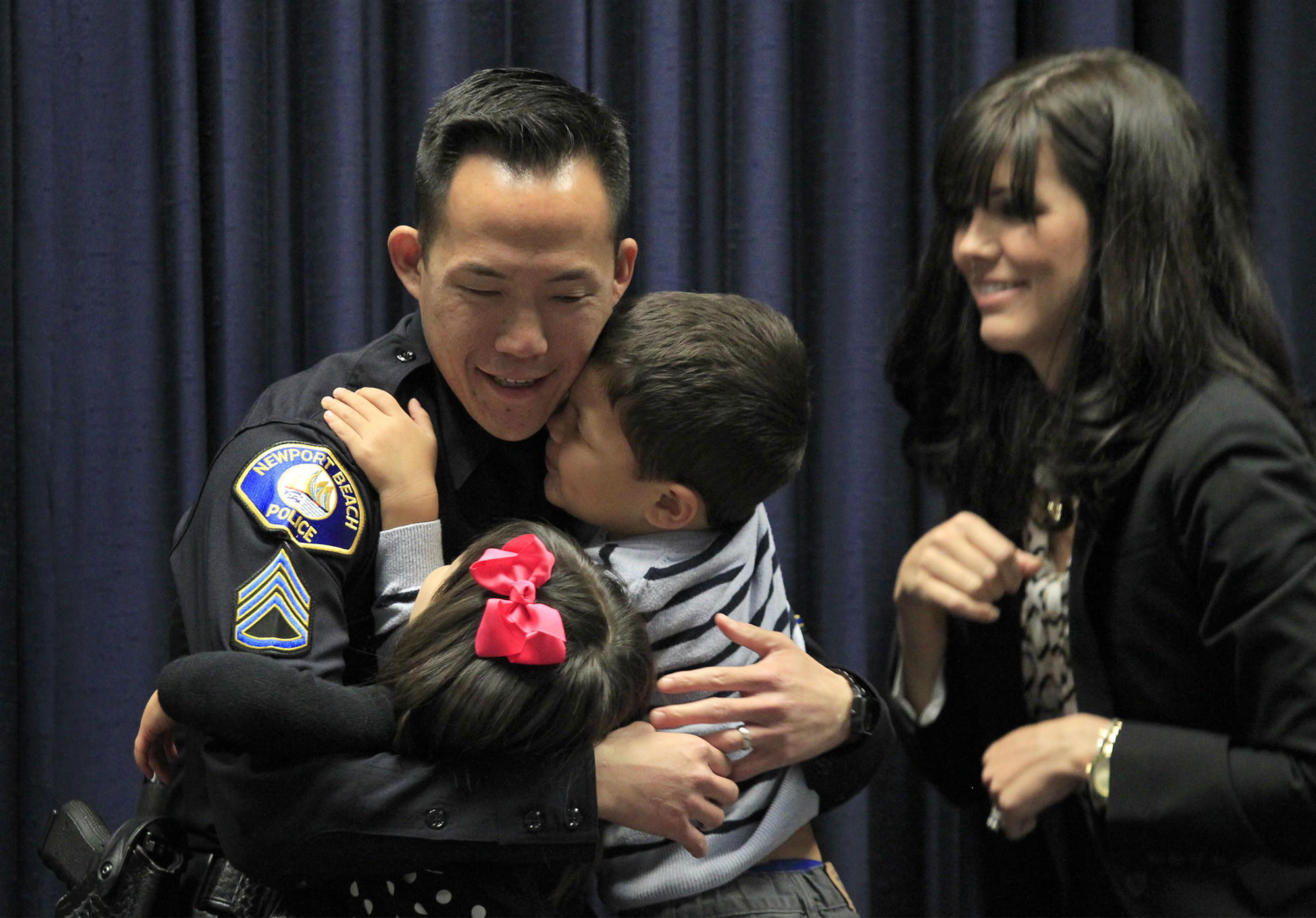 Sgt. Darrin Joe shares a hug with his son Scott, 4, and daughter Whitney, 2, after his wife Wendy, right, pinned his new badge on him during a promotions ceremony at the Newport Beach Police Department on Thursday. (Kevin Chang/ Daily Pilot)