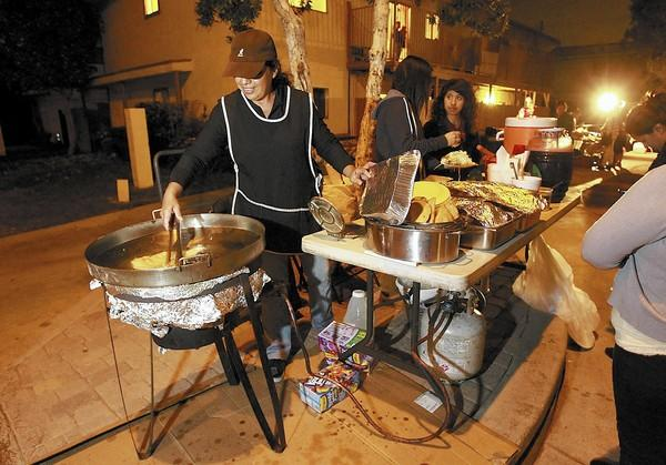 Ana Lara prepares quesadillas before the traditional posada Latino Christmas celebration at Shalimar Park on Wednesday.