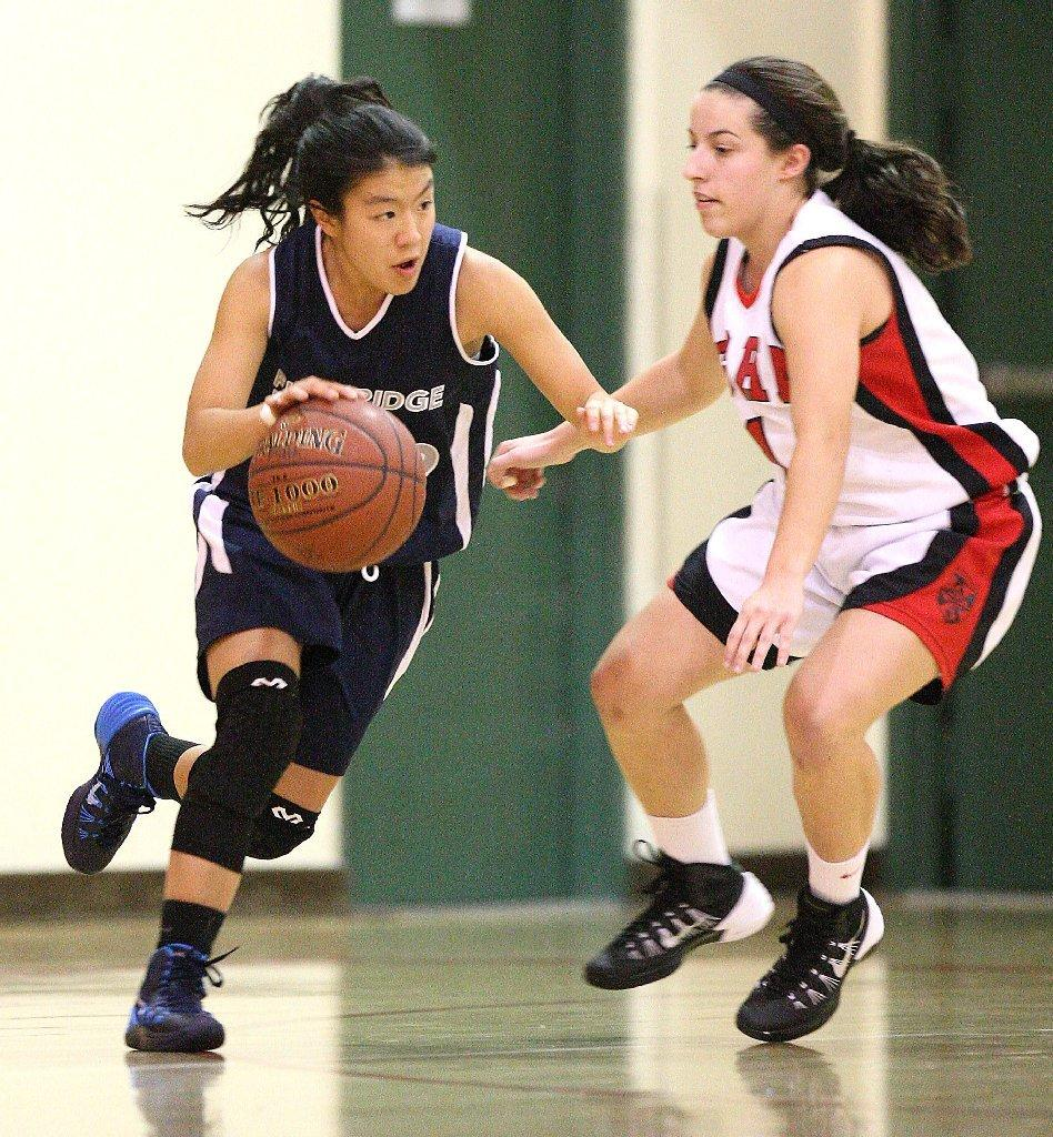 Flintridge Prep's Maya Okamoto drives around Flintridge Sacred Heart's Kelly Fradet during a nonleague crosstown game on Thursday. Flintridge Prep won, 51-33. (Roger Wilson/Staff Photographer)