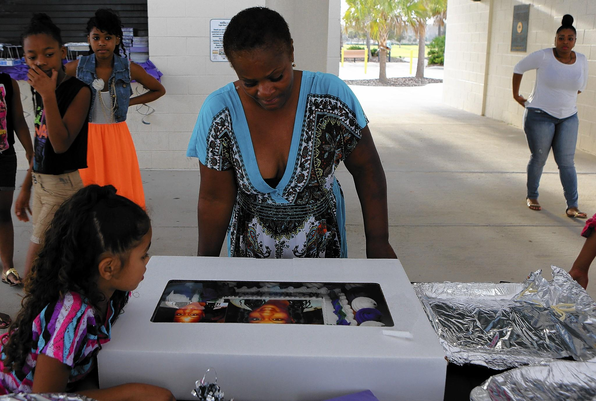 Andrea Wingster looks at a cake bearing a photo of her late daughter, Desire Andre, during a family gathering to commemorate Andre, who was hit by a car on Lee Road last year, leaving her 10 children without the central figure in their lives.