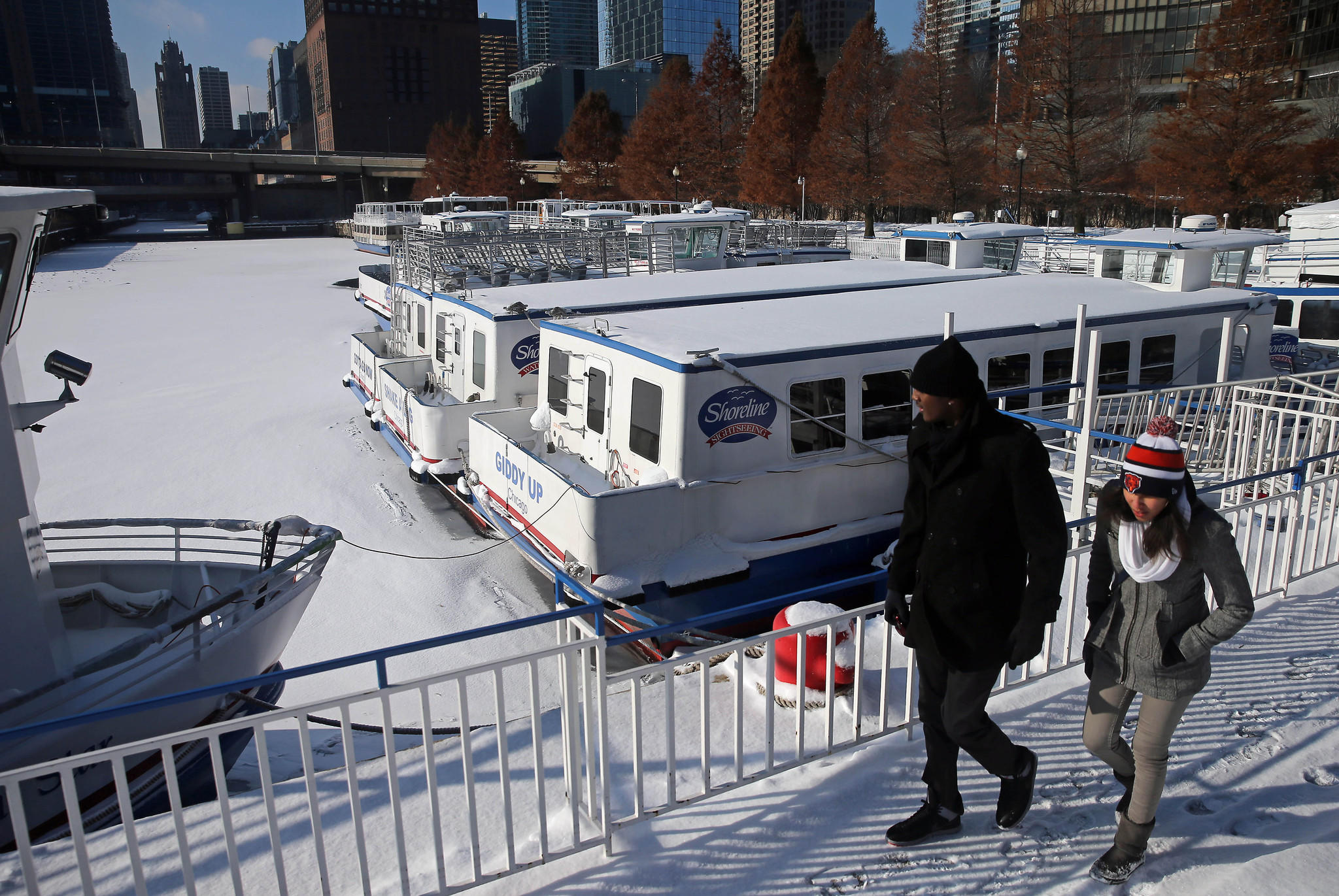 Shoreline cruise boats sit surrounded by ice near Gateway Park at Navy Pier.