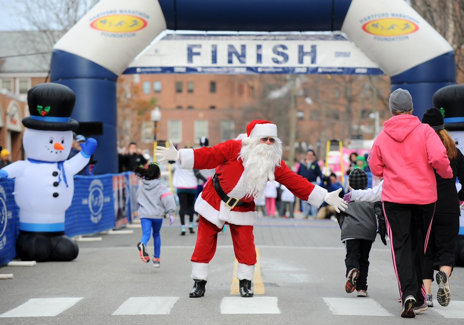 Santa high-fives runners who are about to cross the finish line at the Blue Back Mitten Run on Dec. 8.