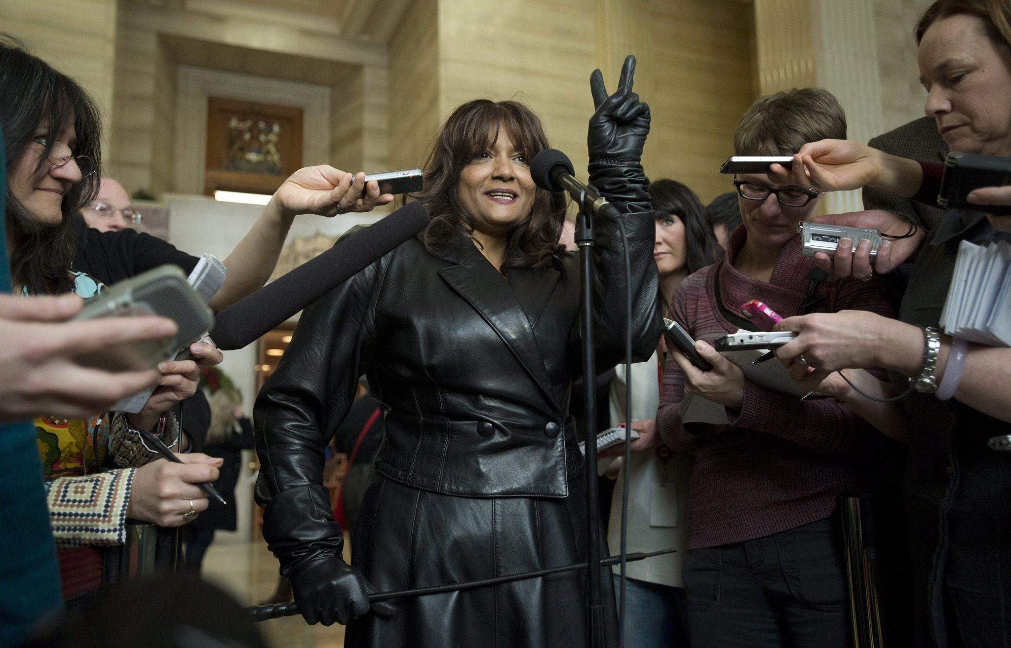 Terri Jean Bedford, in dominatrix garb, flashes a victory sign at the Supreme Court of Canada on Friday after the justices ruled unanimously to strike down laws against prostitution. Bedford and other sex workers argued that the laws constitute arbitrary discrimination and prevent them from practicing their trade safely.